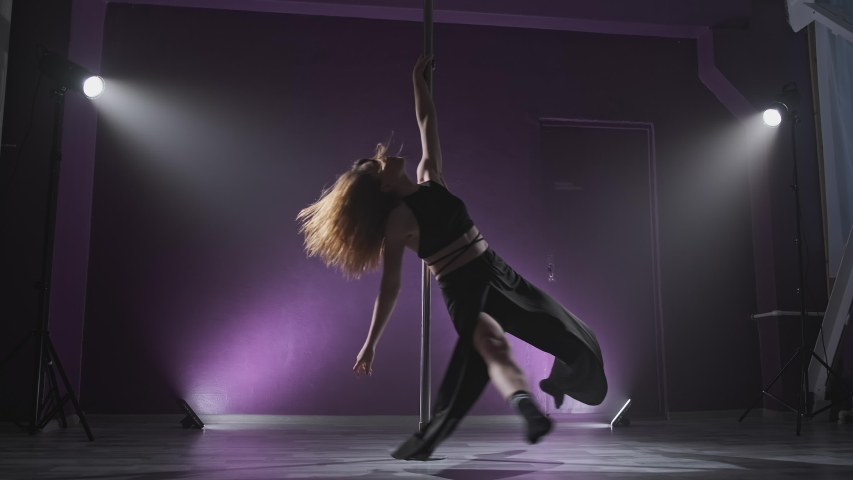 Young slim girl dancing near pole. Beautiful woman performs sensual dance in slow motion. Sexy woman pole dancing in dark interior with lights and smoke in 4K, UHD