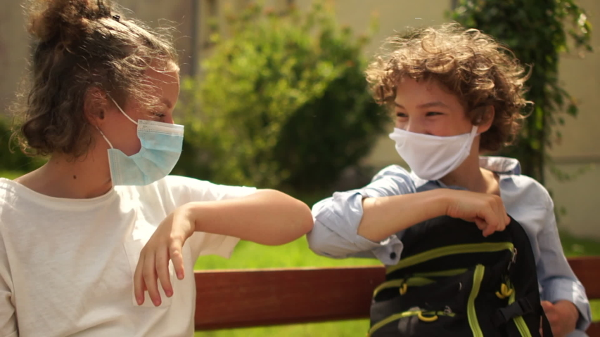 School-age children in medical masks sit on a bench and then say goodbye, touching each other with their elbows. Contactless farewell, back to school after quarantine coronavirus covid-19 | Shutterstock HD Video #1055951732