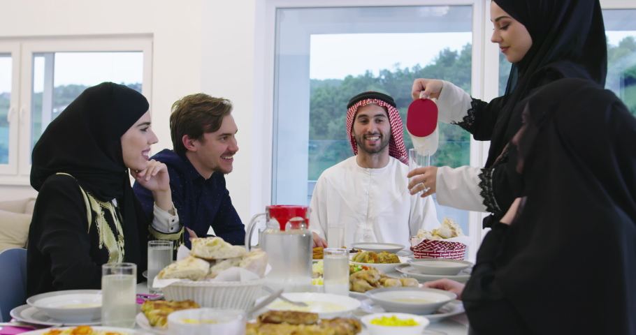Muslim traditional family together having dinner on table at home during Ramadan   Shutterstock HD Video #1055952941