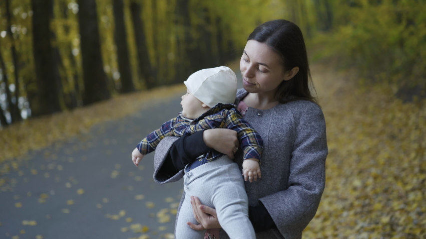 Young, happy mother admires her cute baby boy when holds and lulls him on hands during walk in an autumn park. 4K
