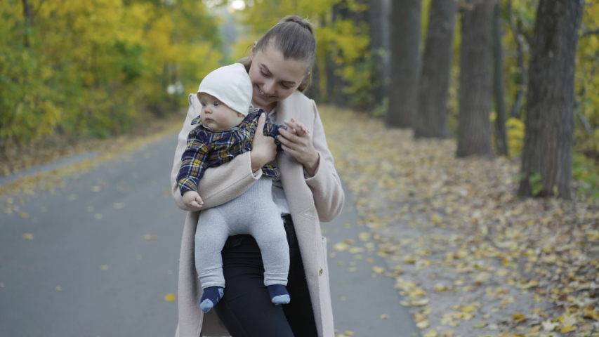 Young, happy mother entertains her cute baby boy when holds and lulls him on hands during a walk in an autumn park. 4K