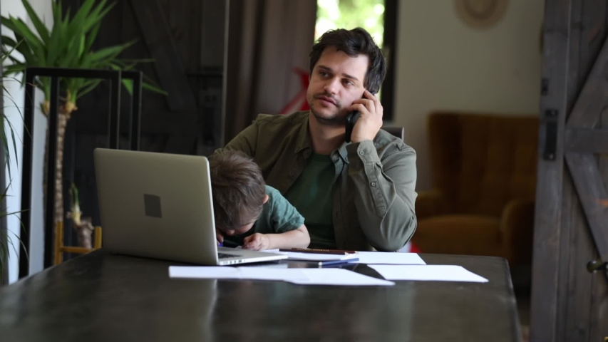 Father is trying to work and play with a little boy at same time at home.  | Shutterstock HD Video #1055960504