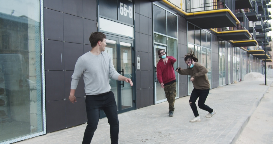 Terrifying male zombies chasing frightened man on the street. Scared young guy running away from creepy hungry walking dead. Apocolypse, halloween, virus, supernatural concept.