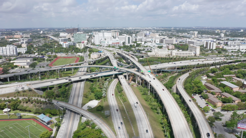 Aerial of rush hour traffic with highway panorama. 4k slow motion transportation and cars above suburban area. Drone flight over multi-level intersection on sunny day. Beautiful Miami city, Florida