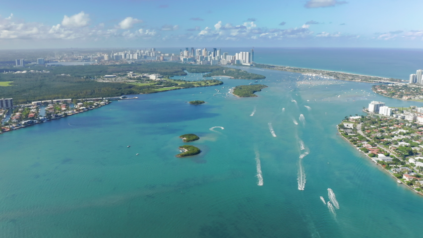 South Beach nature, Florida, USA. 4K aerial panorama of clean light-green sea waters in Miami bay. Residential front line buildings with beautiful Atlantic ocean view. Background for travel business
