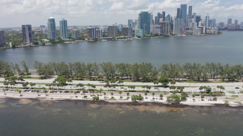 4K aerial of busy two-direction roads at the Miami bay. Drone view on modern residential and business frontline buildings with ocean view. 4K video of Miami, Florida, USA