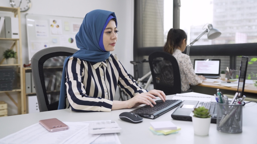 Busy serious puzzled muslim woman employee sitting in coworking shared office with diverse multicultural colleague holding mobile phone talking with client solving problem distantly. mad malay worker Royalty-Free Stock Footage #1055968946