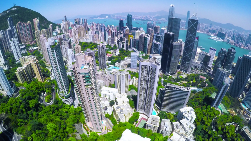 Aerial Hong Kong of China with Beautiful Clear Sky. 4K Aerial view of the famous Hong Kong Island. Forward shot flying over office buildings and skyscrapers.