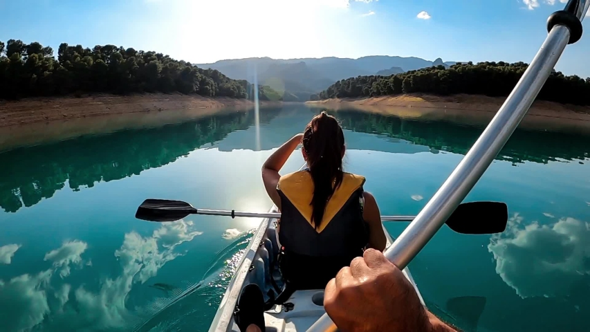 Kayak rowing slow motion. Kayaker woman and man kayaking in beautiful landscape at Embalse de la Bolera, Spain. Kayakers practice sports in a kayak at the lake. Aquatic sports during summer