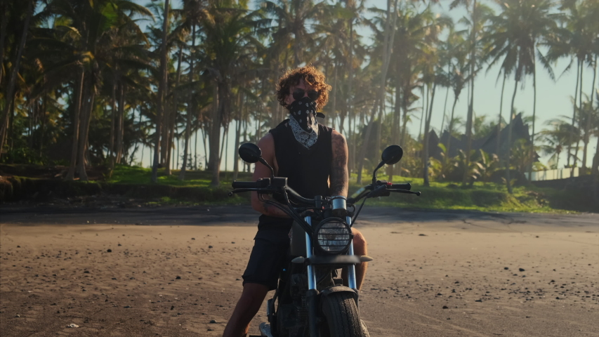 Portrait of a bold tattooed biker taking off bandana mask sitting on his motorbike. View on the beach against tropical palms. Free and self-reliant   Shutterstock HD Video #1055980124