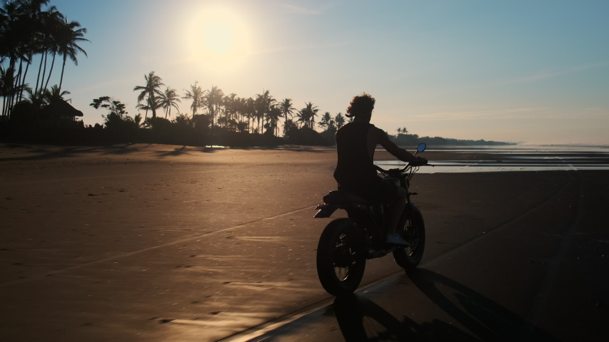 Scenic slow motion shot of man biker riding along the black sand beach of Bali in the warm light of evening sun. Feel free being away from hustle | Shutterstock HD Video #1055980178