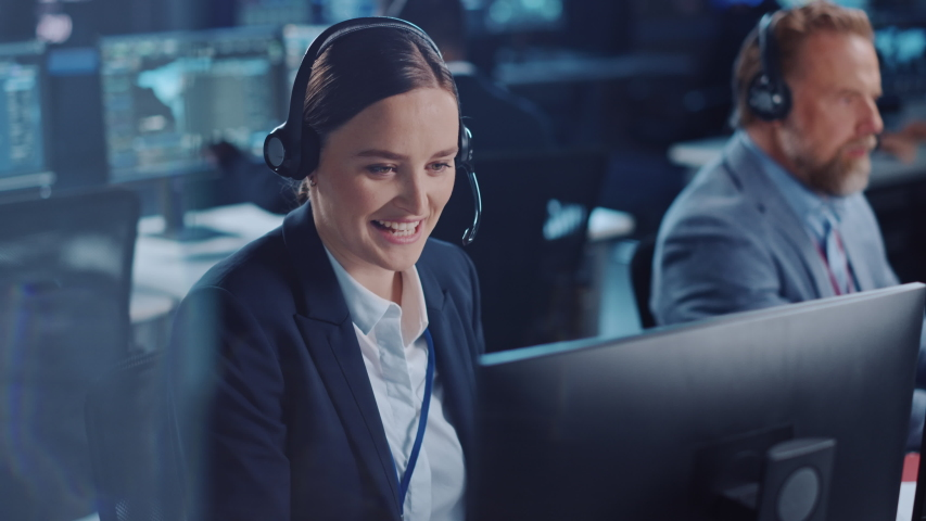 Happy Beautiful Technical Customer Support Specialist is Talking on a Headset while Working on a Computer in a Dark Monitoring and Control Room Filled with Colleagues and Display Screens. Royalty-Free Stock Footage #1055986550