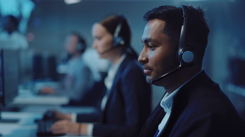 Close Up Portrait of a Joyful Technical Customer Support Specialist Talking on a Headset while Working on a Computer in a Call Center Control Room Filled with Computer Display Screens and Data Servers Royalty-Free Stock Footage #1055986598