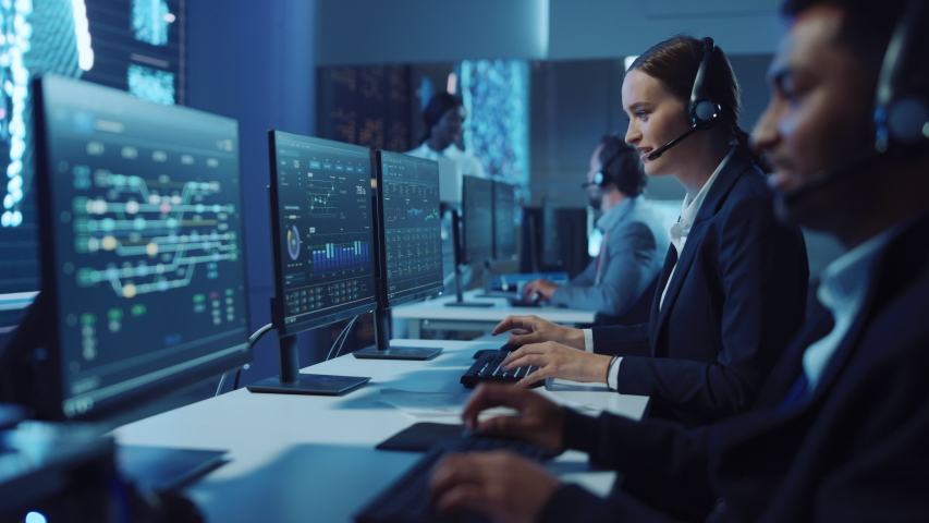 Happy Confident Technical Customer Support Specialist Having a Headset Call while Working on a Computer in a Dark Monitoring and Control Room Filled with Colleagues and Display Screens. Royalty-Free Stock Footage #1055986619