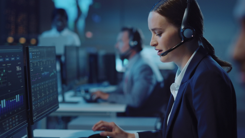 Shifting Focus from a Young Female Technical Support Specialist to a Handsome Indian Colleague Talking on a Headset while Working on a Computer in Call Center Control Room Filled with Displays. Royalty-Free Stock Footage #1055986622
