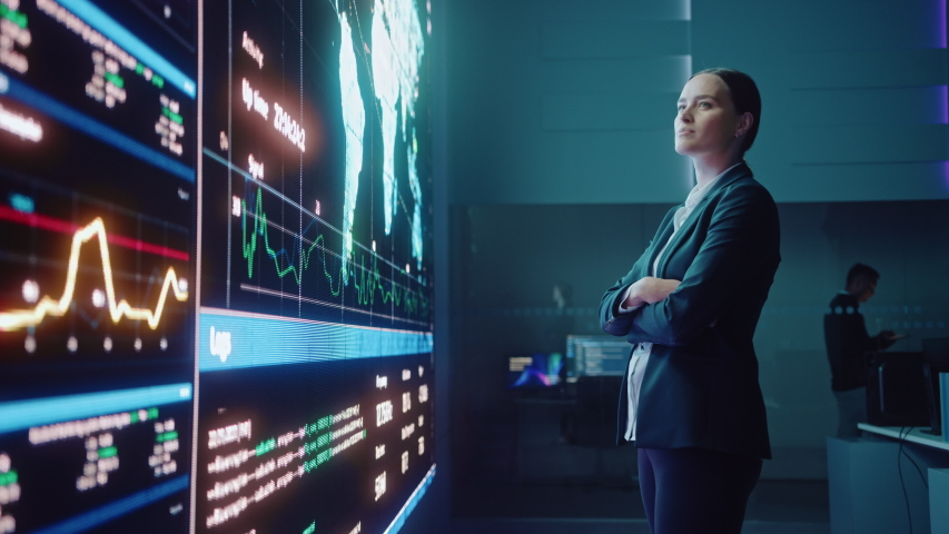 Young Female Computer Science Engineer Looking at Big Screen Display Showing Global Map with Data Points. Telecommunications Technology Company System Control and Monitoring Room with Servers. Royalty-Free Stock Footage #1055986637