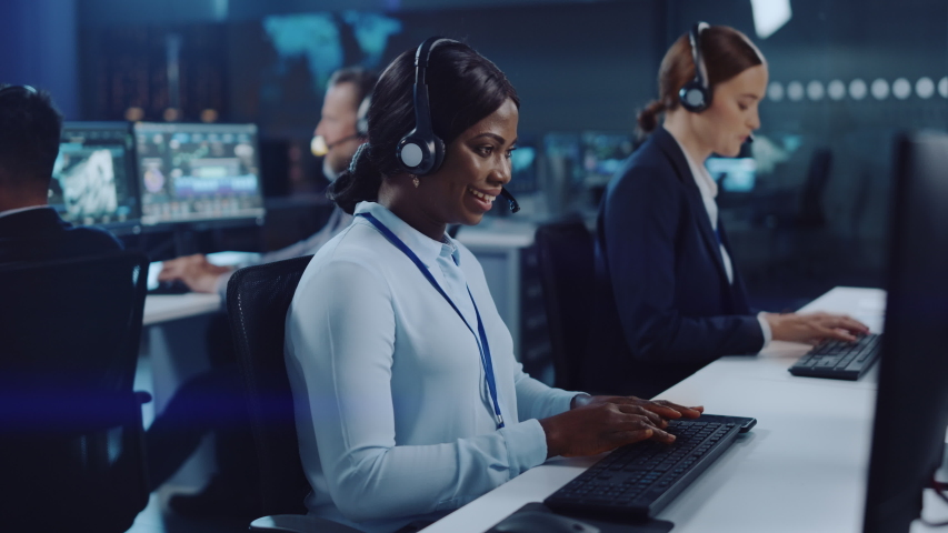 Happy Beautiful Technical Customer Support Specialist is Talking on a Headset while Working on a Computer in a Call Center Control Room Filled with Colleagues, Display Screens and Data Servers. Royalty-Free Stock Footage #1055986667