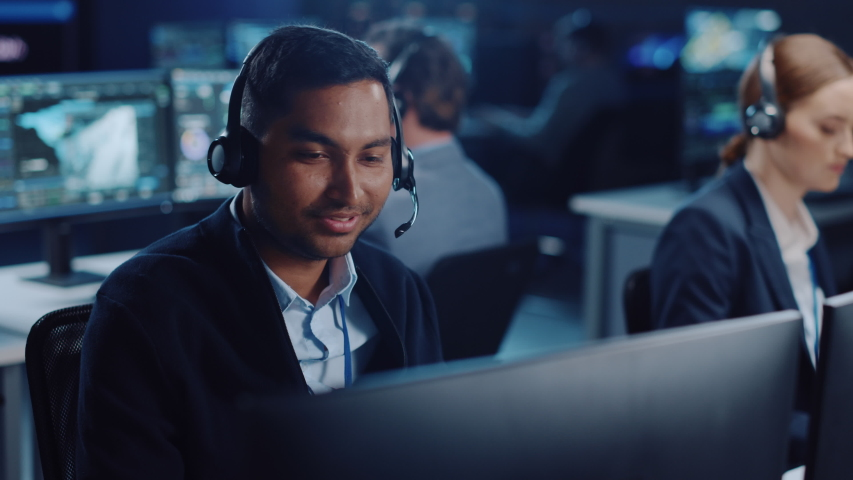 Close Up Portrait of a Joyful Technical Customer Support Specialist Talking on a Headset while Working on a Computer in a Call Center Control Room Filled with Computer Display Screens and Data Servers Royalty-Free Stock Footage #1055986709