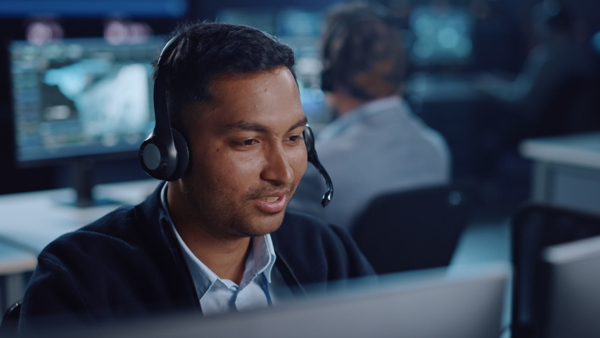Close Up Portrait of a Joyful Technical Customer Support Specialist Talking on a Headset while Working on a Computer in a Call Center Control Room Filled with Computer Display Screens and Data Servers Royalty-Free Stock Footage #1055986712