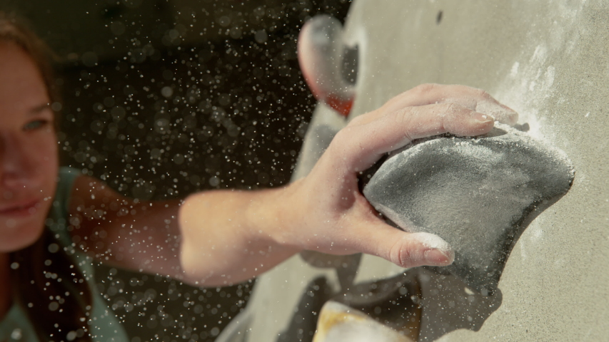 SLOW MOTION, MACRO, DOF: Tiny particles of white chalk fly in the air as the young female climber grips a grey hold. Teenage girl reaches and grips a gray pinch hold with her magnesium covered hand. Royalty-Free Stock Footage #1055987153