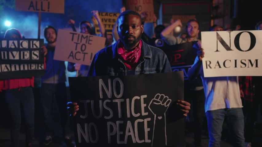 Serious strike afro-american man leader with invocatory poster standing in front of determined multi-ethnic crowd protesting against police violence. Black lives matter. Royalty-Free Stock Footage #1055988674