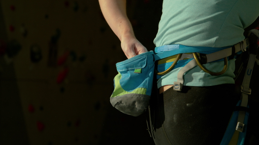 SLOW MOTION, CLOSE UP, DOF: Young climber girl flicks her fingers to remove excess magnesium. Unrecognizable woman rock climbing in an indoor training facility chalks up her hands before climbing. Royalty-Free Stock Footage #1055988989