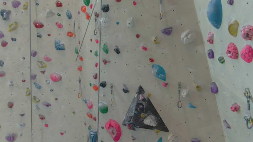 AERIAL: Aerial view of the high walls of a climbing gym filled with colorful magnesium-covered holds. Flying around an empty indoor rock-climbing training center closed due to the covid-19 outbreak. Royalty-Free Stock Footage #1055988995