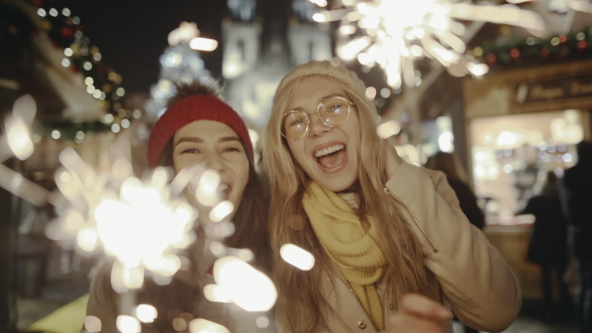 Pretty young girlfriends laughing and dancing with sparklers in the street . Smiling women walking at the festive fair on New Year's Eve in New York. Being happy together and making dreams come true.