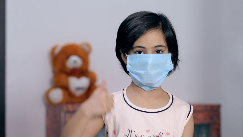 Portrait of a young girl using a medical mask during the Covid-19 pandemic time. Cute Indian kid wears a surgical mask and shows a thumbs-up sign to protect herself from dangerous coronavirus Royalty-Free Stock Footage #1055994851