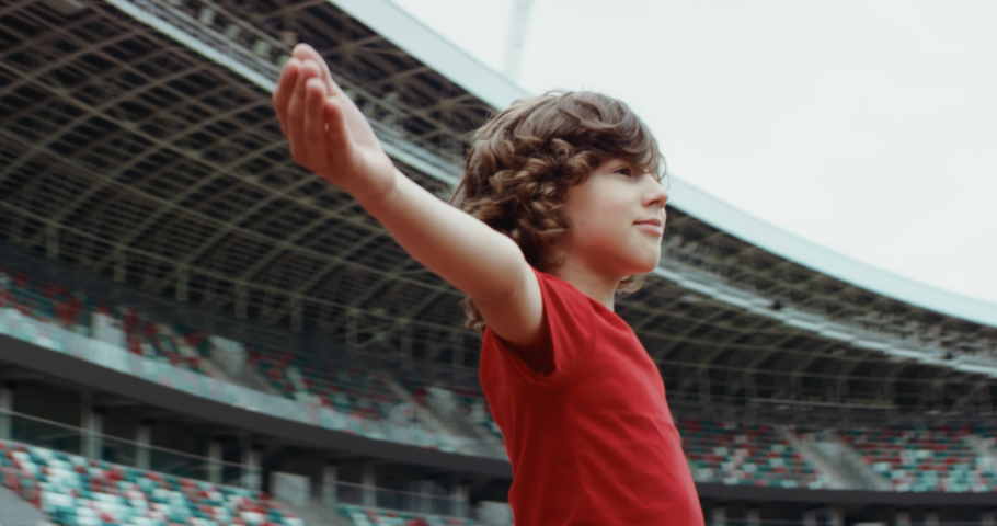 Cute little kid boy soccer player spreading hands on an empty stadium, dreaming of becoming professional player, soccer star. RED cinema camera RAW graded footage Royalty-Free Stock Footage #1055995286