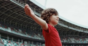 Cute little kid boy soccer player spreading hands on an empty stadium, dreaming of becoming professional player, soccer star. RED cinema camera RAW graded footage