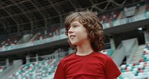 Cute little kid boy soccer player standing on an empty stadium, dreaming of becoming professional player, soccer star. RED cinema camera RAW graded footage