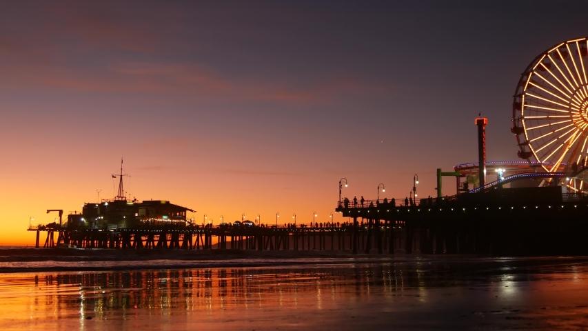 Twilight waves against classic illuminated ferris wheel, amusement park on pier in Santa Monica pacific ocean beach resort. Summertime iconic symbol of California glowing in dusk, Los Angeles, CA USA