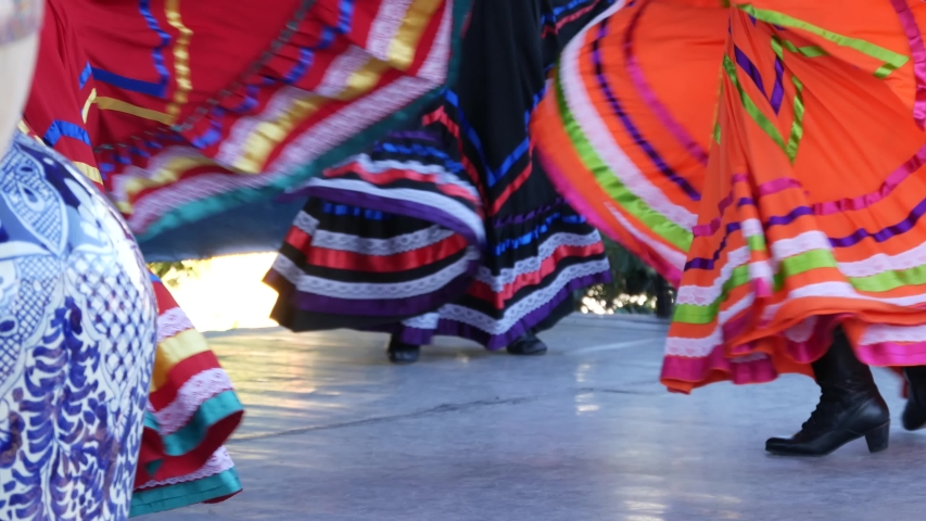Latino women in colourful traditional dresses dancing Jarabe tapatio, mexican national folk hat dance. Street performance of female hispanic ballet in multi colored ethnic skirts. Girls in costumes. Royalty-Free Stock Footage #1055997953