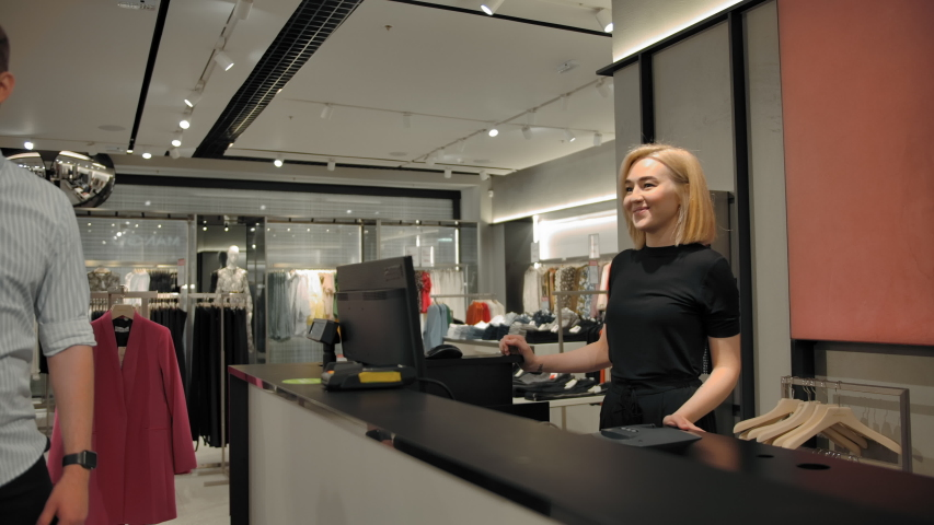 Young handsome cashier seller taking customer's cloth for packing. Lovers couple, guy and a girl are shopping in the store. Middle shot. Spacious retail of clothing and shoes Royalty-Free Stock Footage #1056002240