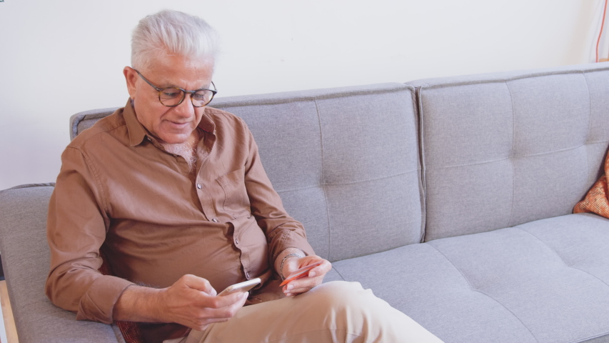 Smiling older man holding credit card and smartphone sitting on couch at home. Happy male shopper using instant easy mobile payments making purchase in online store. E-banking app service Royalty-Free Stock Footage #1056005177