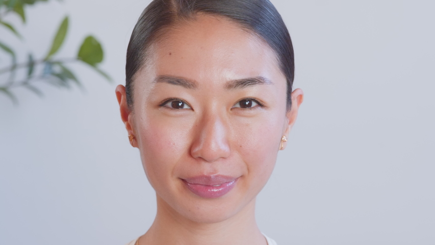 Confident smiling young adult Asian woman looking at camera sitting at home office. Happy millennial casual professional lady with pretty face posing for close up portrait indoors.