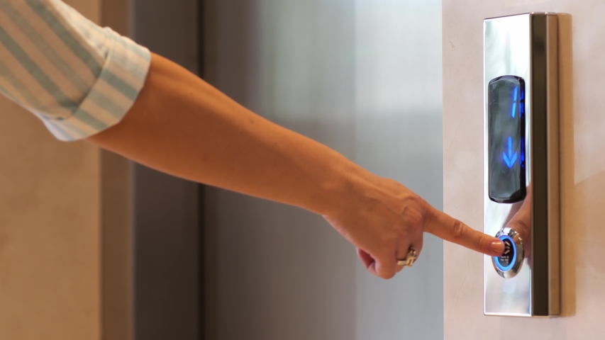 Female hands in medical protective gloves pressing elevator button. Young woman touches lift buttons. Disease prevention during quarantine, hygiene. Close up.