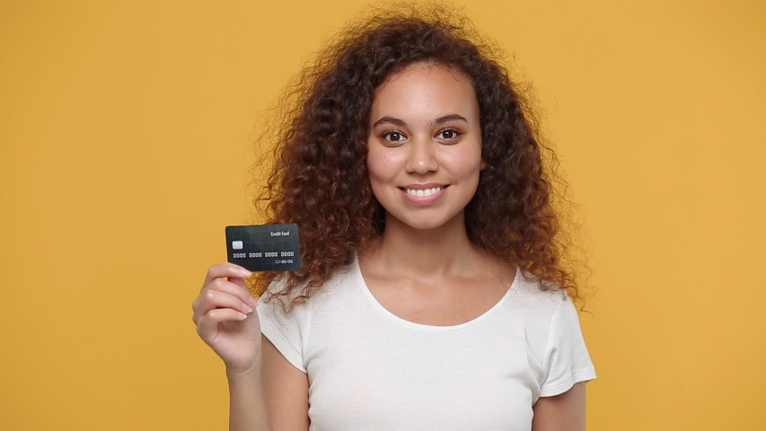 Young happy african american girl 20s years old in white t-shirt isolated on yellow background studio. People lifestyle concept. Looking camera hold in hand bank credit card showing thumbs up gesture Royalty-Free Stock Footage #1056010196