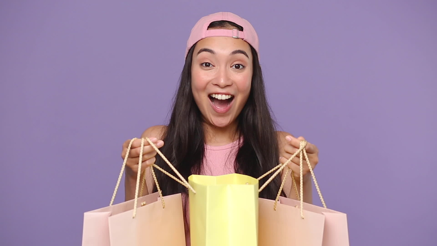 Young asian girl 20s years old in casual pink clothes cap hold in hands look into package bags with purchases after shopping isolated on pastel purple violet background studio People lifestyle concept Royalty-Free Stock Footage #1056010769