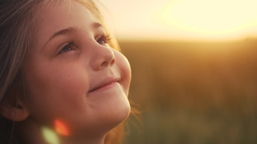 Happy little girl child looking up eyes dream. kid wants a dream come true portrait at sunset. baby daughter look up silhouette dreaming of a happy childhood. kid free face sister side view thinks