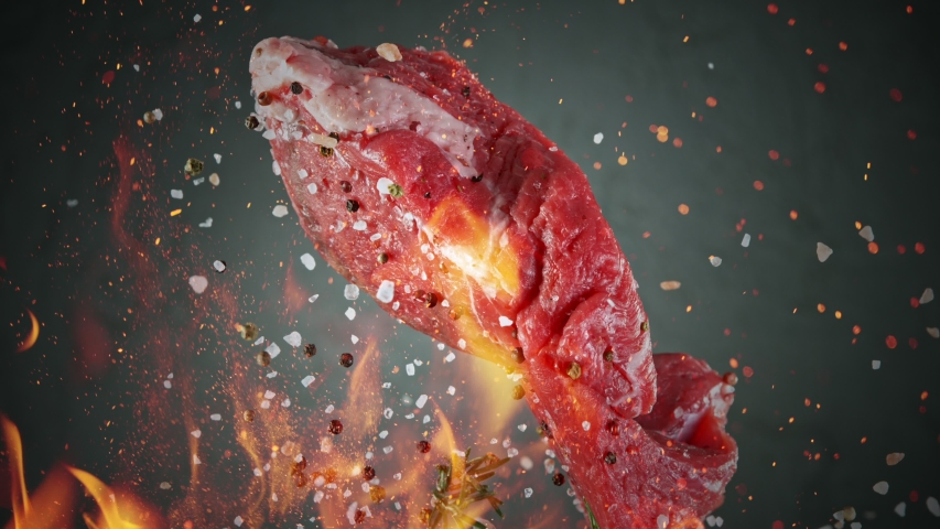 Close-up of falling tasty beef steak, super slow motion, filmed on high speed cinematic camera at 1000 fps.