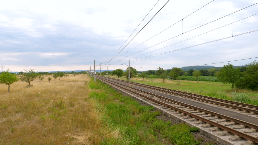 Wallau, Germany - July 14, 2020: Tracking crane shot of a passing ICE train on the highspeed line Frankfurt - Cologne near Wallau. ICE is a highspeed train system in Germany