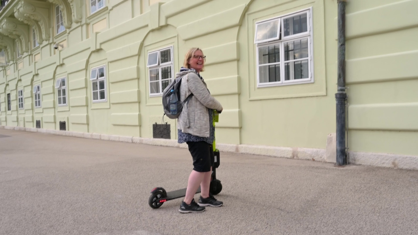 VIENNA - JULY 11, 2019: A happy woman rides a rental electric scooter | Shutterstock HD Video #1056012809
