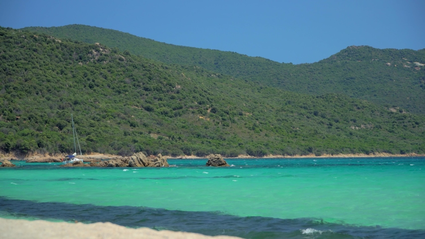 Amazing view of the rocky beach on a sunny day. Azure clear clear water, Corsica, France. Beautiful views of the panorama from boats and yachts. A man is swimming in the water. Luxury holidays. island