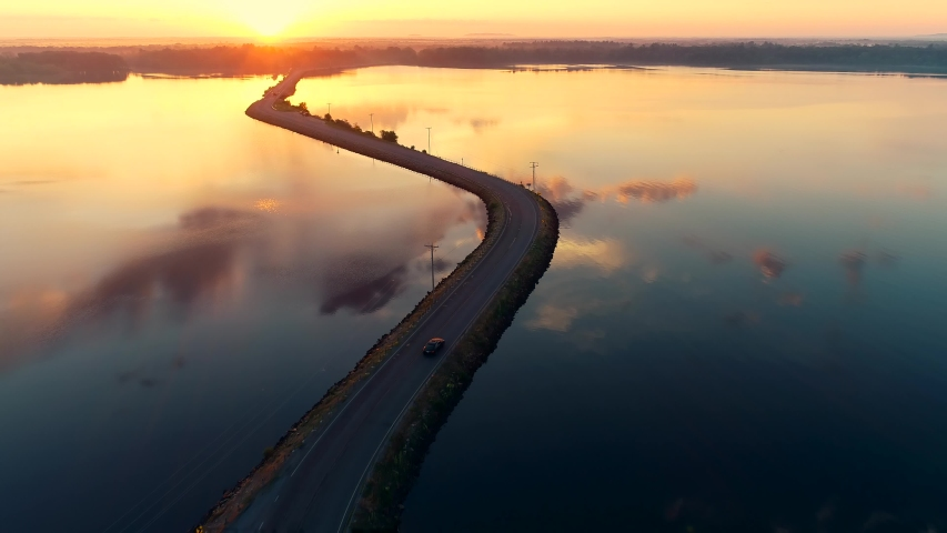 Aerial drone shot of a car driving on a bridge or causeway over a lake at sunrise as the sun peeks over trees on the horizon and clouds reflect in the surface of the water. Royalty-Free Stock Footage #1056020504