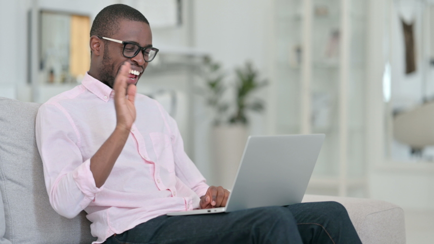 Attractive African Man doing Video Call on Laptop at Home  | Shutterstock HD Video #1056022997