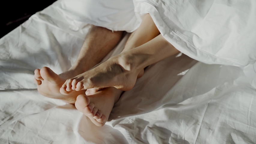 Couple in bed making love. male and female legs top view, white linens. sex