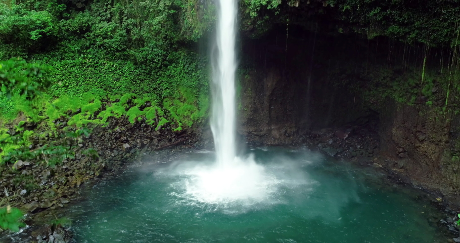 La Fortuna Waterfall in the rainforest near Arenal Volcano in Costa Rica, Central America. Beautiful nature landscape at toursit travel destination landmark. Aerial drone video footage.