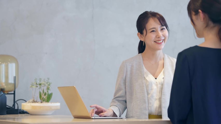 Young asian receptionist talking with customers. Hotel worker. Store clerk. Royalty-Free Stock Footage #1056025280